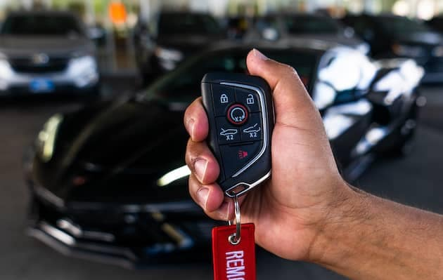 A shot of a person's hand holding a car key.