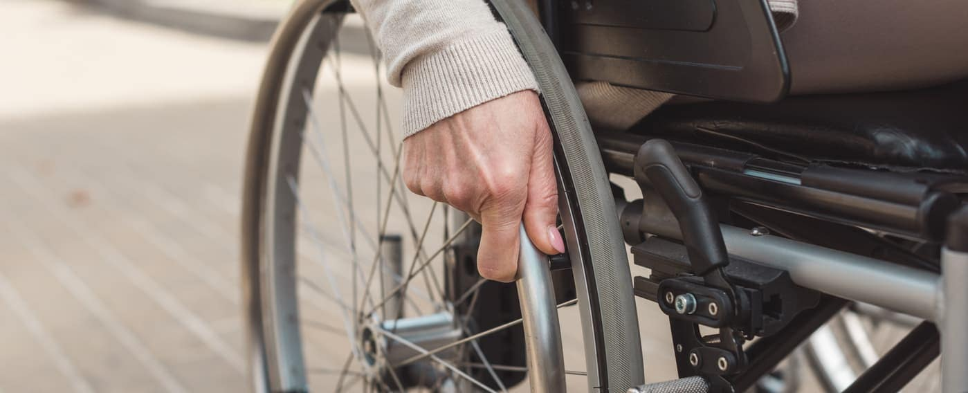 close up of wheelchair wheel with woman's hand on wheel