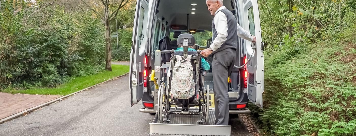 man assisting person into wheelchair van