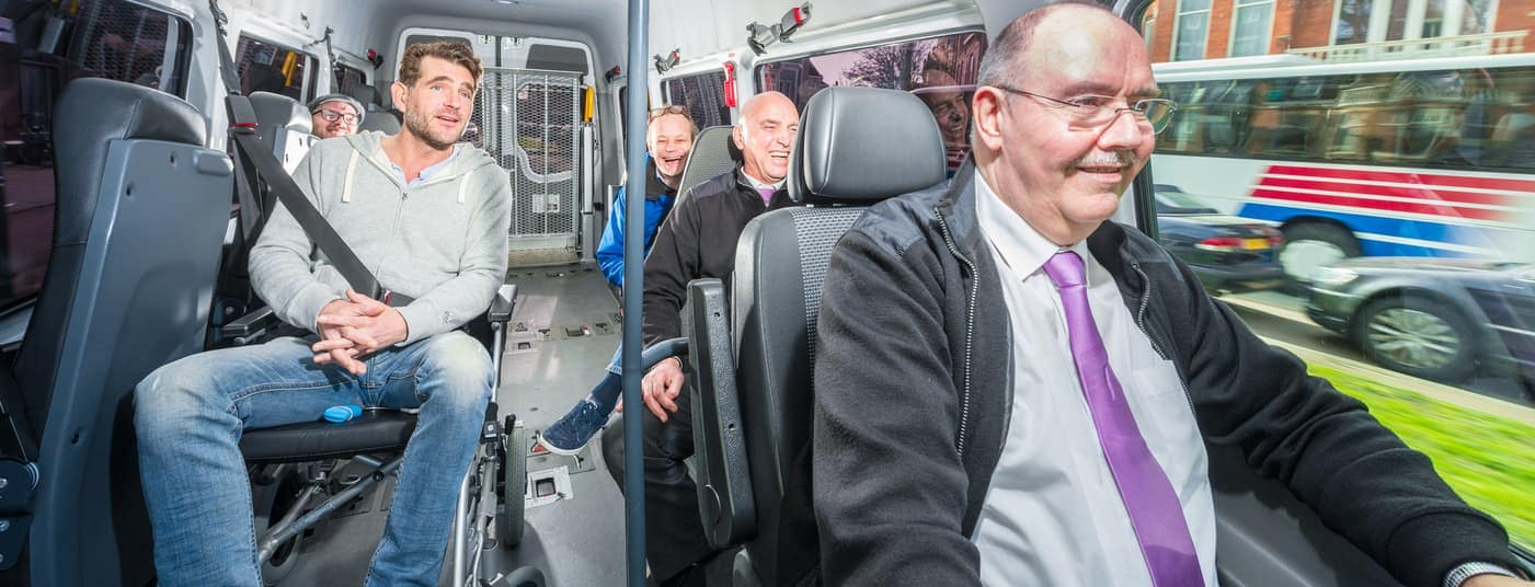 Man riding in wheelchair conversion van with passengers