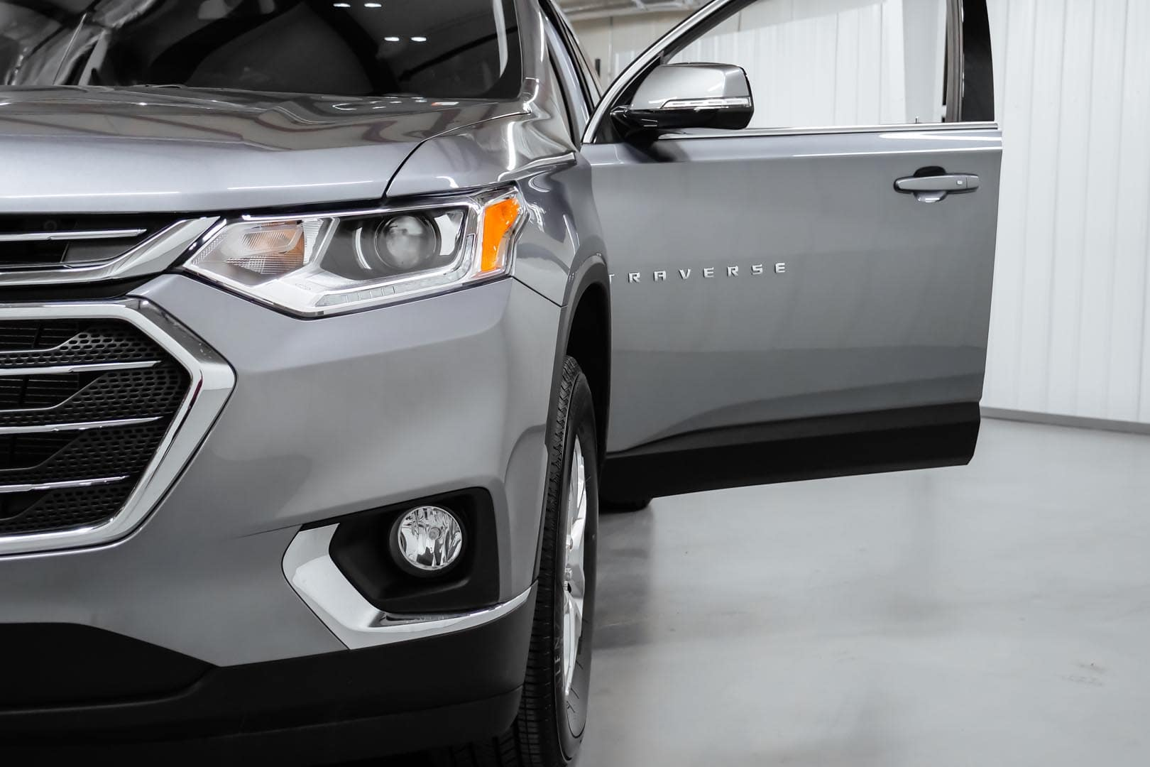 Silver Chevrolet Traverse with open driver side door