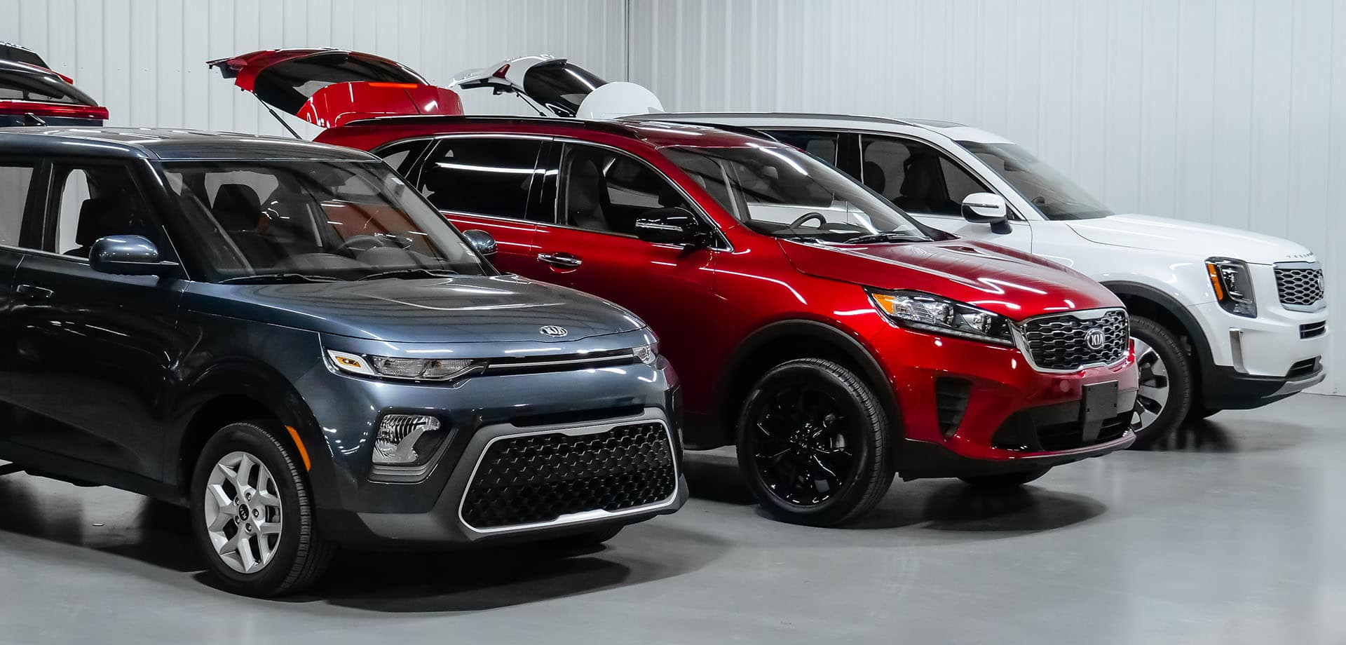 Row of three wheelchair accessible Kia SUVs with open trunks