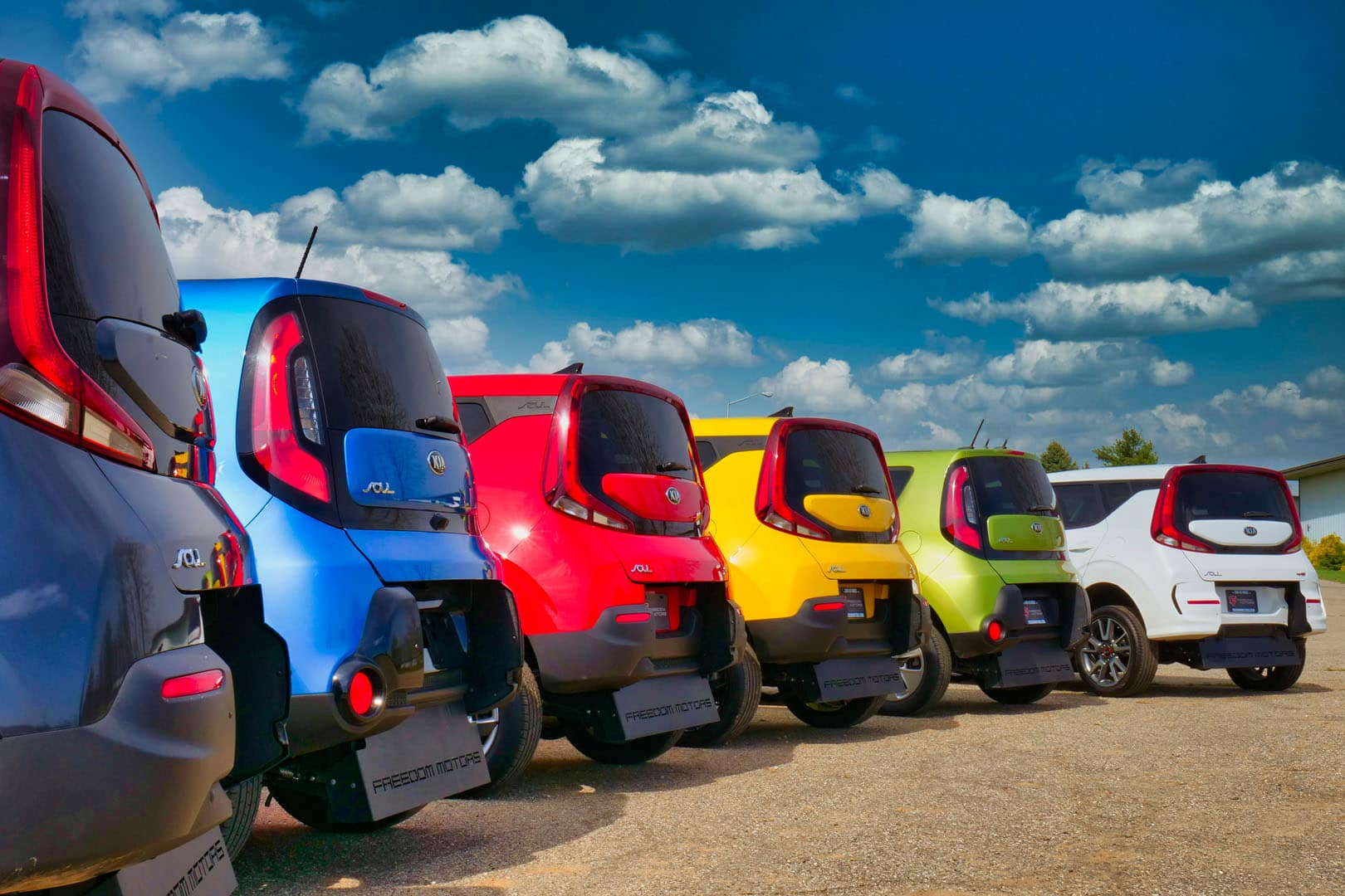 A rainbow-colored row of wheelchair accessible Kia Souls.