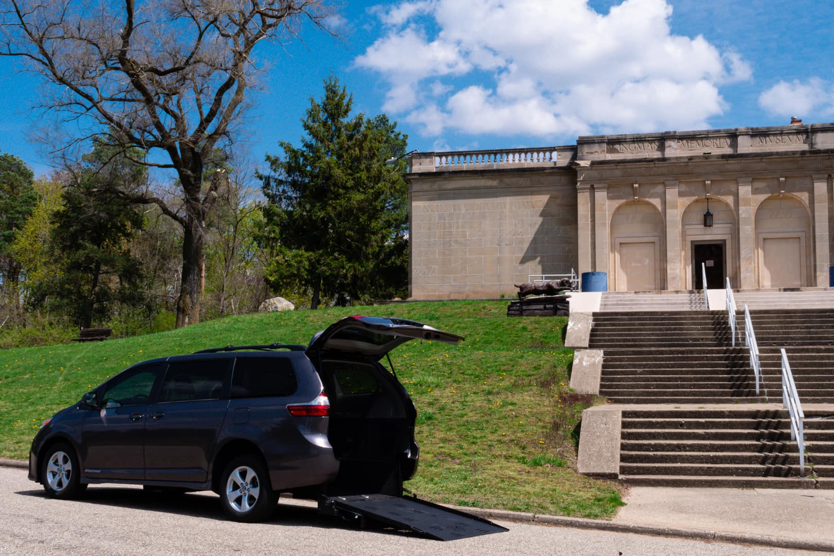 A wheelchair accessible Toyota Sienna outdoors with the ramp deployed.