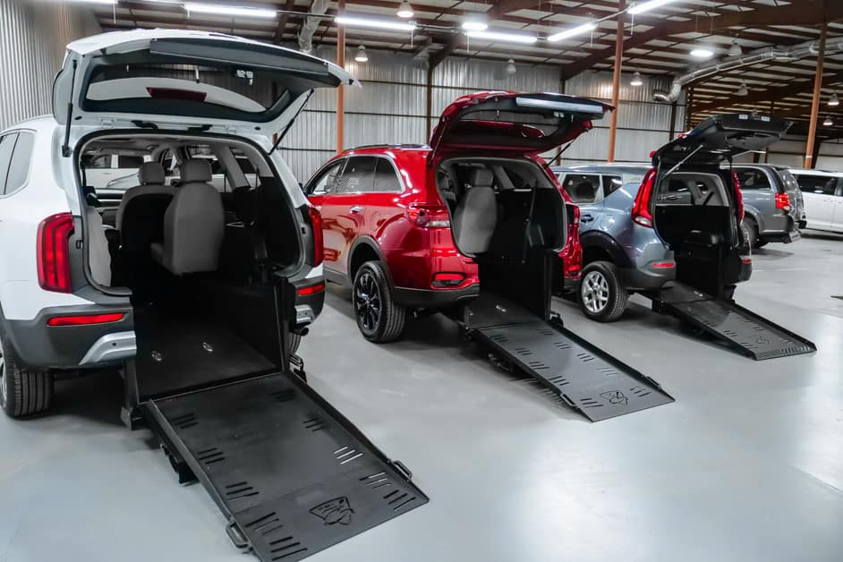 Three wheelchair accessible Kia vehicles from Freedom Motors lined up with ramps deployed