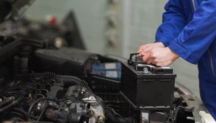 Mechanic's hands installing new car battery