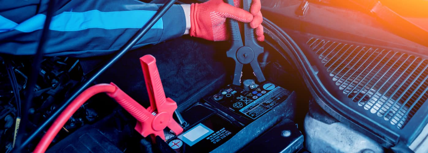 Gloved hand applying jumper cables to car battery
