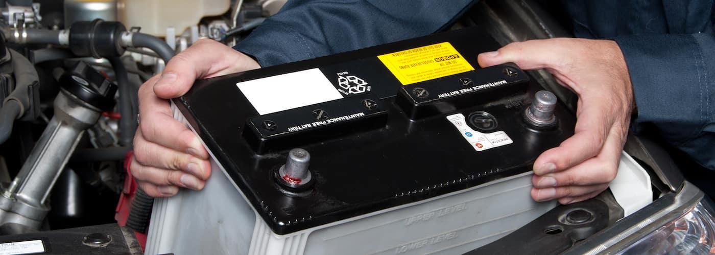 Technician's hands removing dead car battery