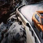 Orange Nissan Rogue driving on snowy mountain highway