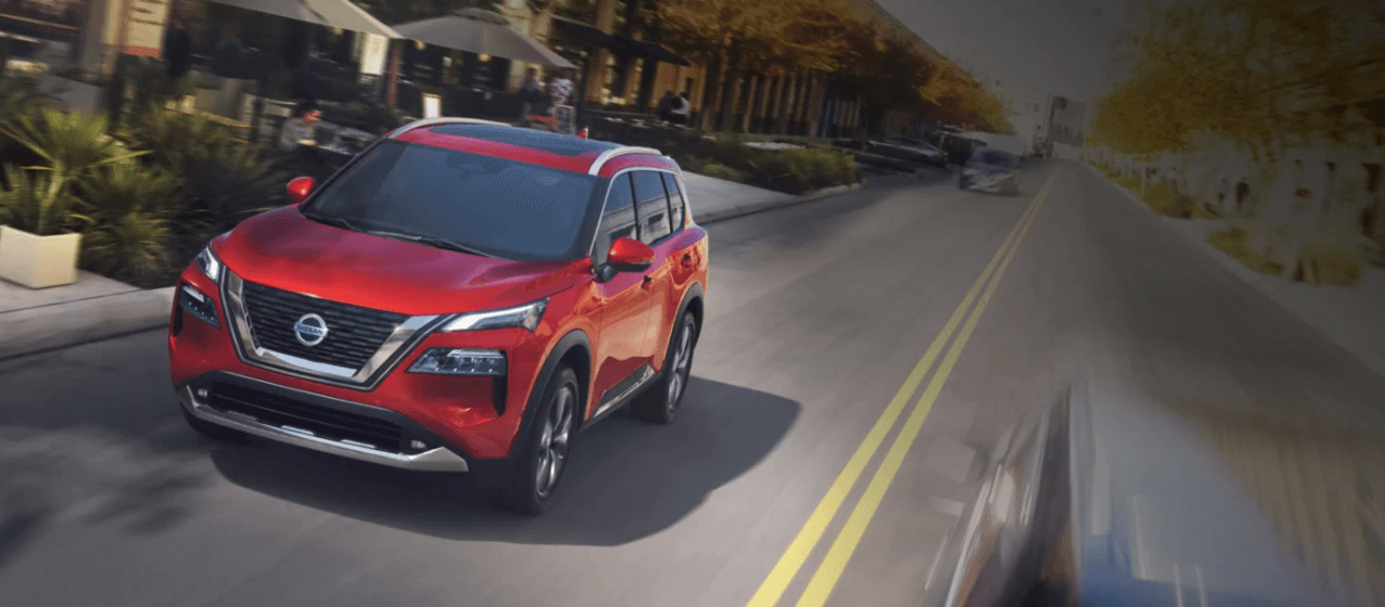 red Nissan Rogue driving in city