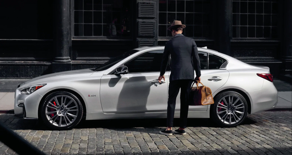 A young man getting into a 2020 INFINITI Q50