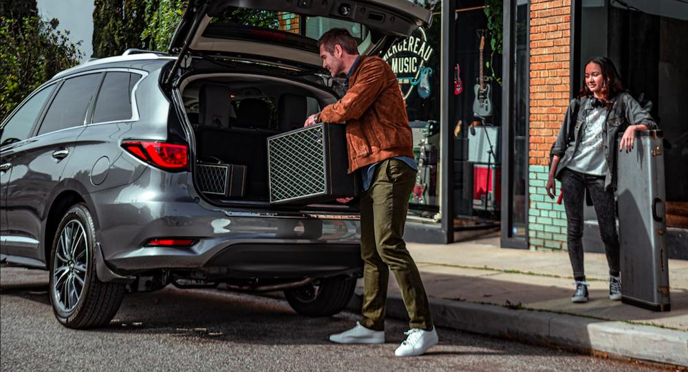 A man loading a guitar amplifier into an INFINITI QX60