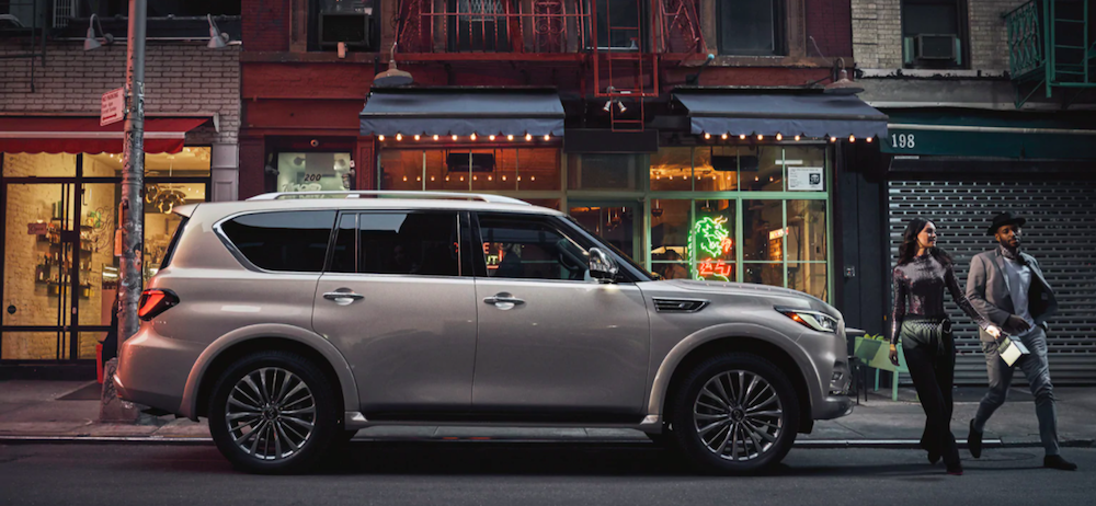 A young couple walking away from their 2021 INFINITI QX80