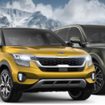 Kia SUVs parked in foreground with mountains in background