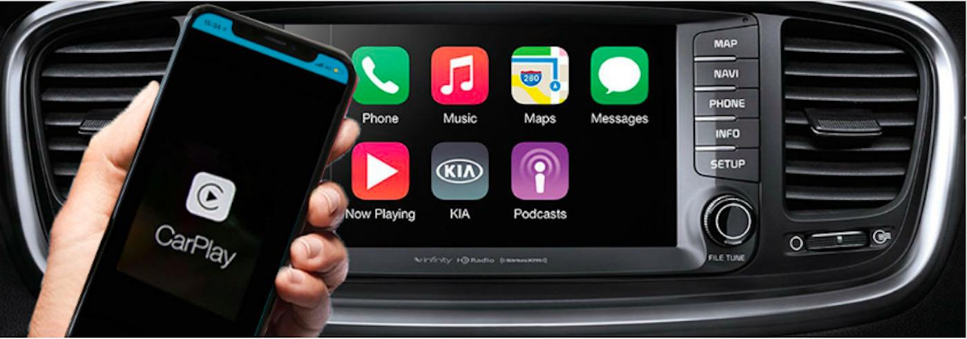 Hand holding iPhone near Kia Sorento Apple CarPlay interface