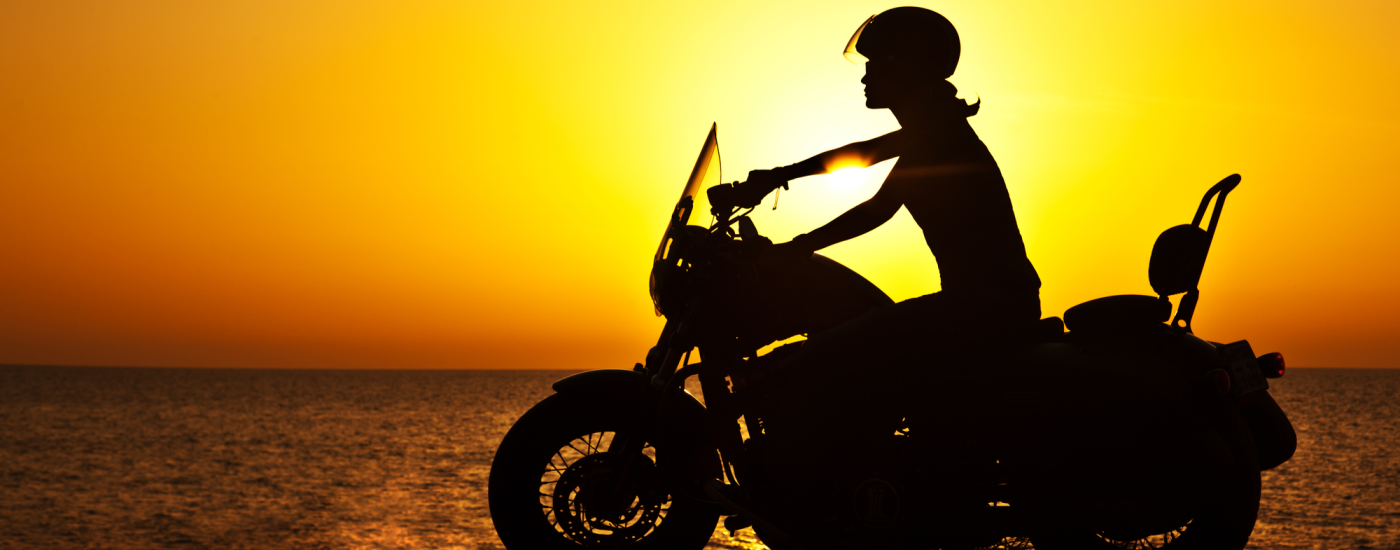Woman driving motorcycle in sunset