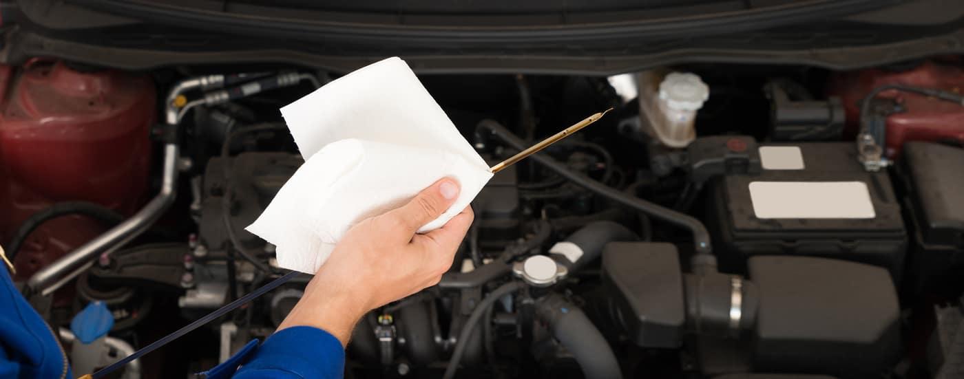 mechanic holding oil dipstick