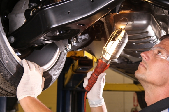 automotive technician inspects under vehicle with light