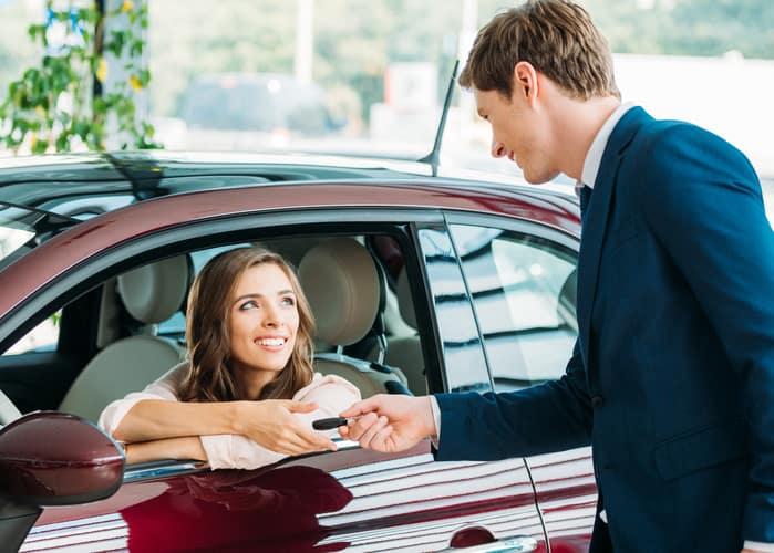 Customer in car handing over car keys to dealer