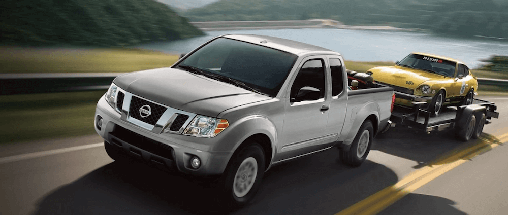 2020 Nissan Frontier towing trailer loaded with vintage car