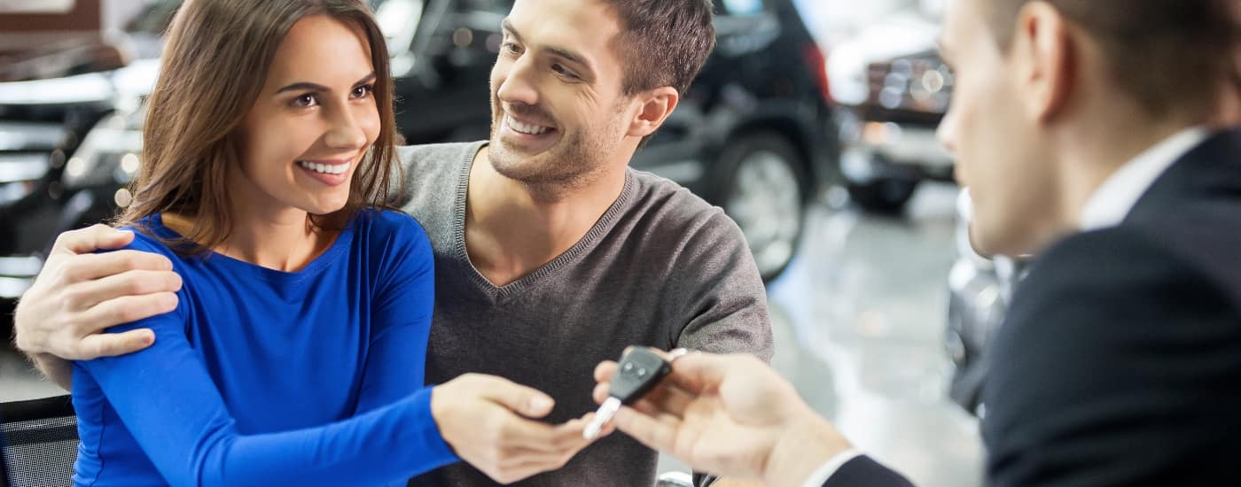man and woman with car salesman