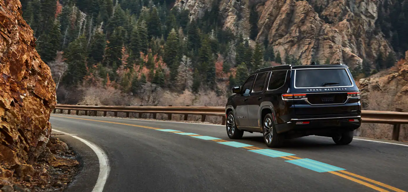 2022 Jeep Wagoneer driving away on mountain road
