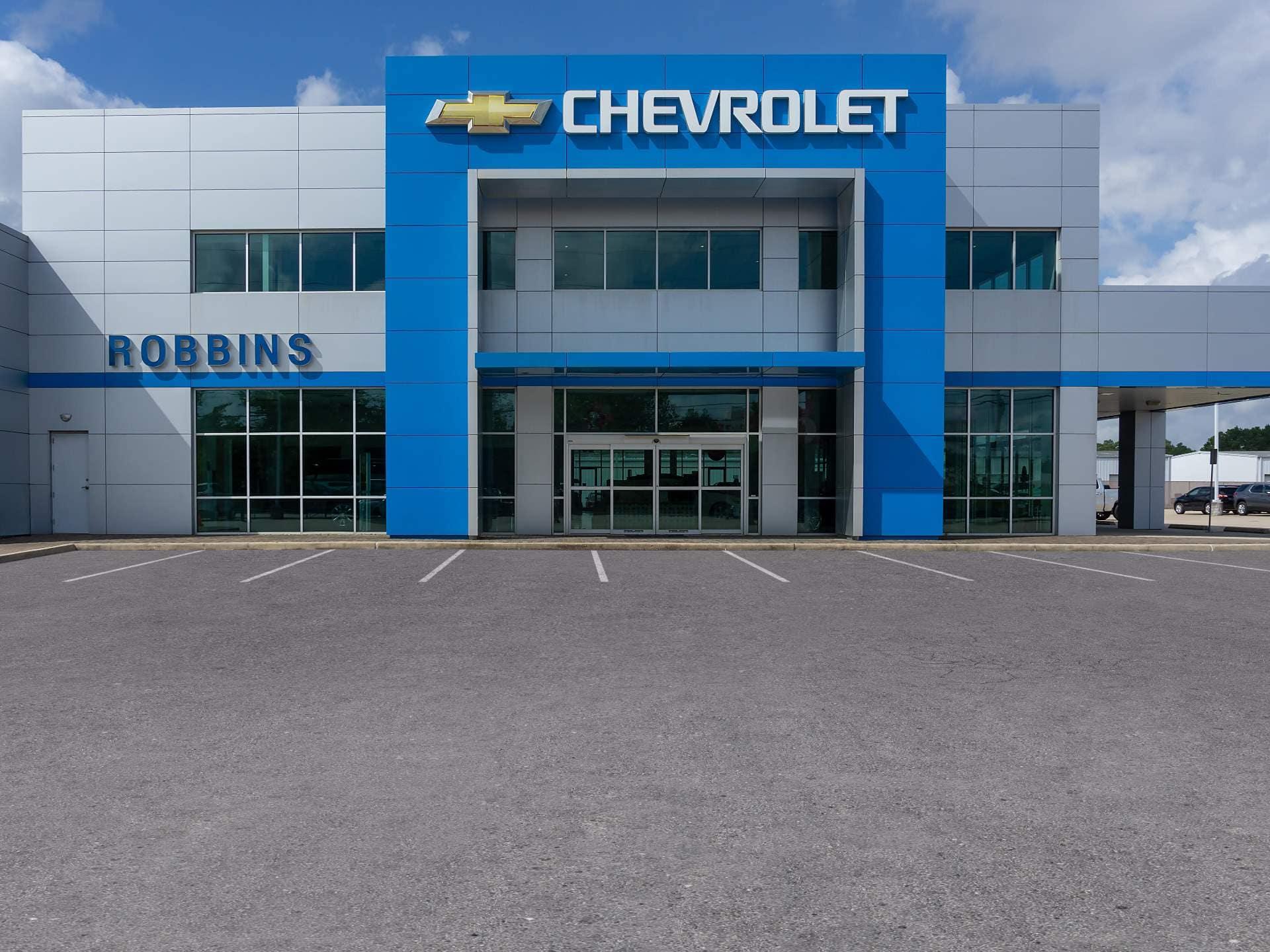 An exterior shot of a Chevrolet dealership at night.