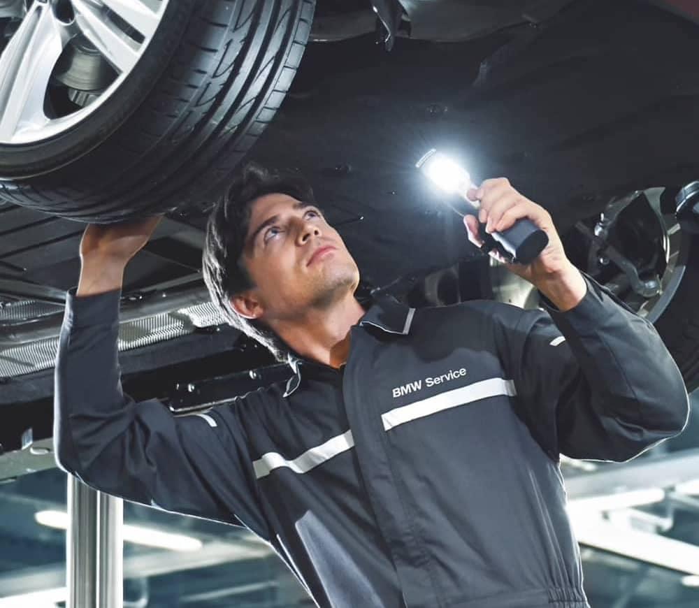 technician looking under vehicle