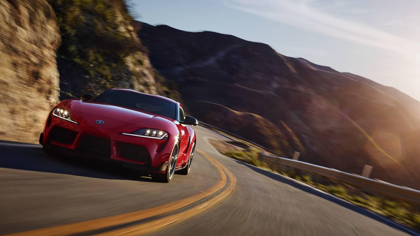 2020 red supra driving on a winding road