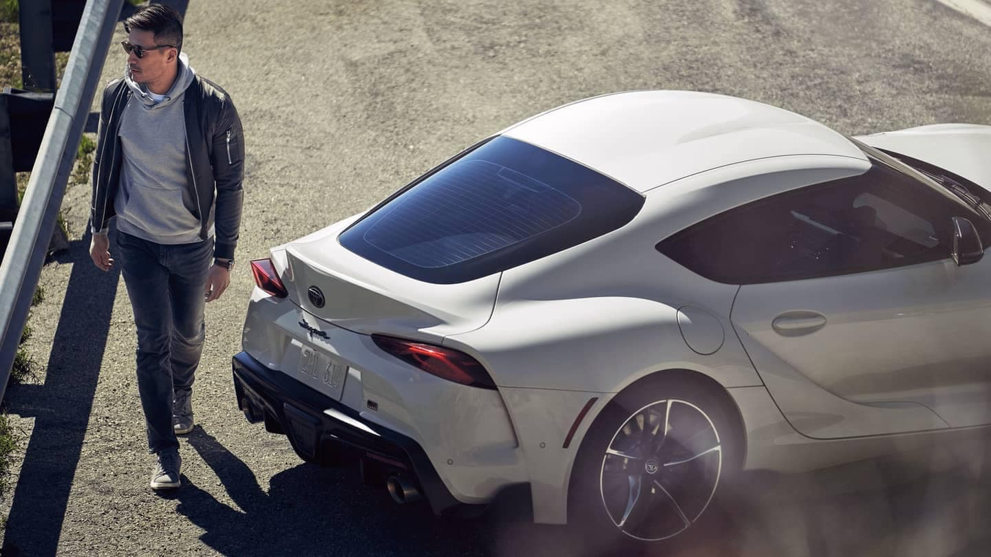 a man standing on the road next to white supra