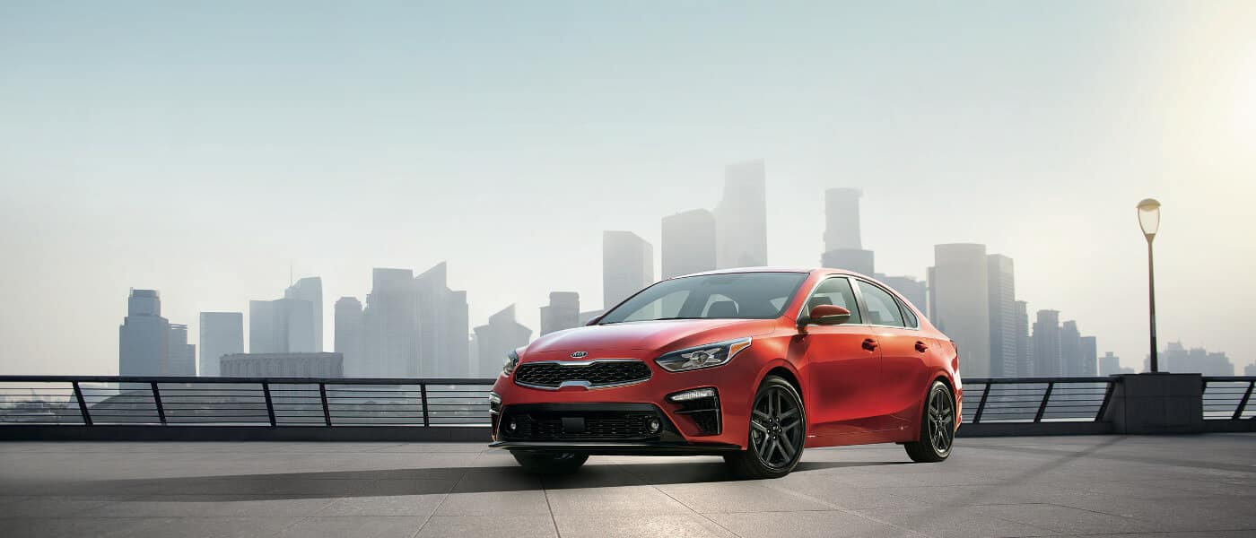 2020 Kia Forte in orange parked on lookout with city in the background