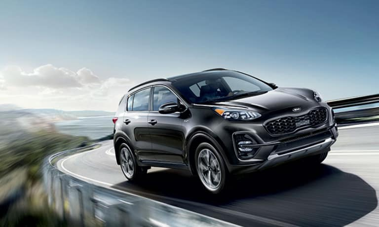 2020 Sportage in black driving on bridge curve in the mountians