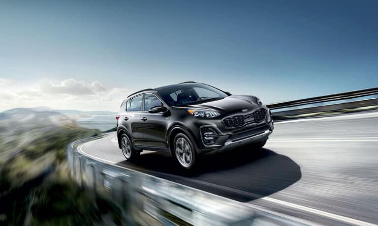 2020 Kia Sportage in black driving on highway in the mountians