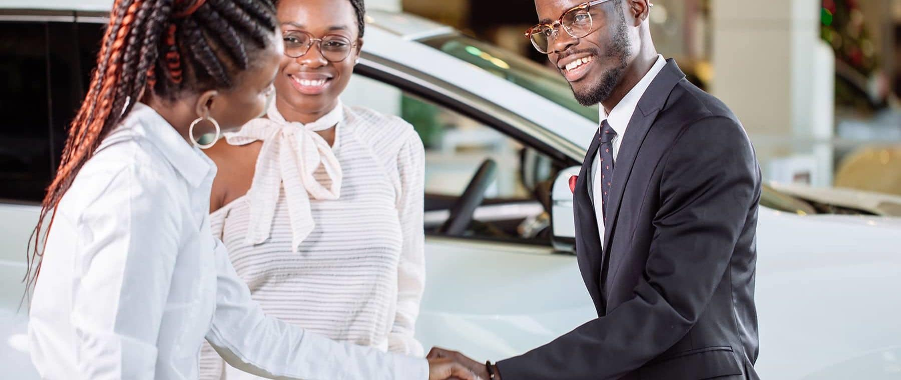 couple shaking hands with car saleswoman