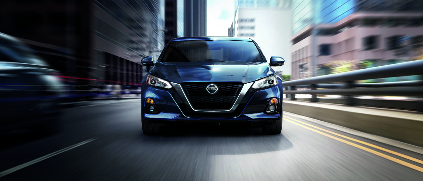 2020 Nissan Altima in blue head on view while driving on a city street