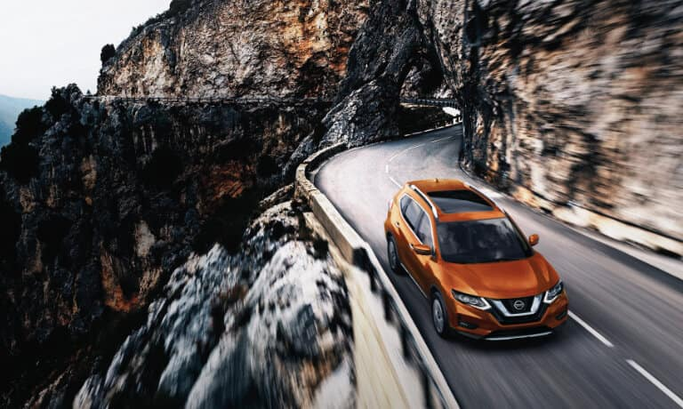 2020 Nissan Rogue in orange driving along a mountian side
