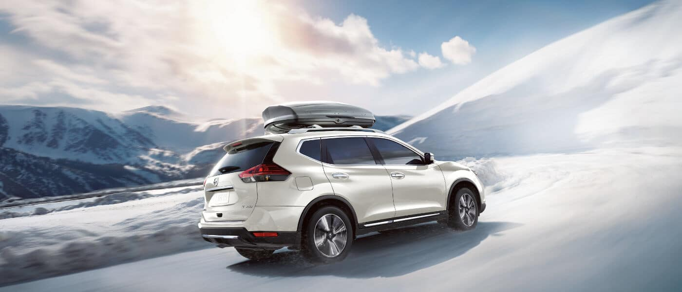 2020 Nissan Rogue in white driving in the snow in the mounitans off road