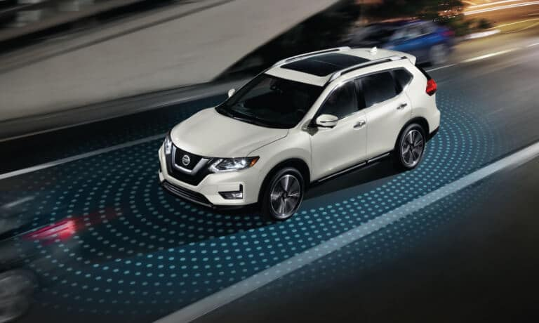 2020 Nissan Rogue in white driving showing saftey sensors