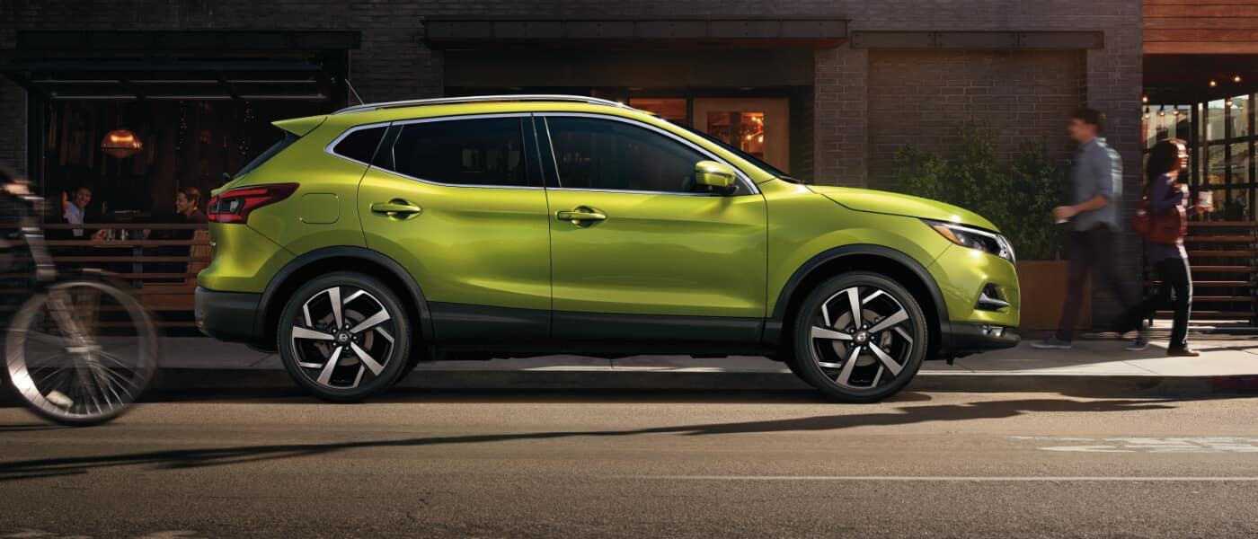 2020 Nissan Rogue Sport in green parked on the side of the road in green infront on a resturant