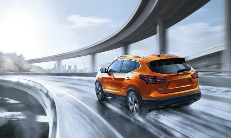 2020 Nissan rogue Sport in orange driving on wet highway