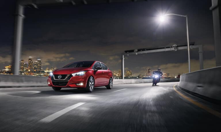 2020 Nissan Versa Exterior Driving On The Highway Next To A Motorcycle