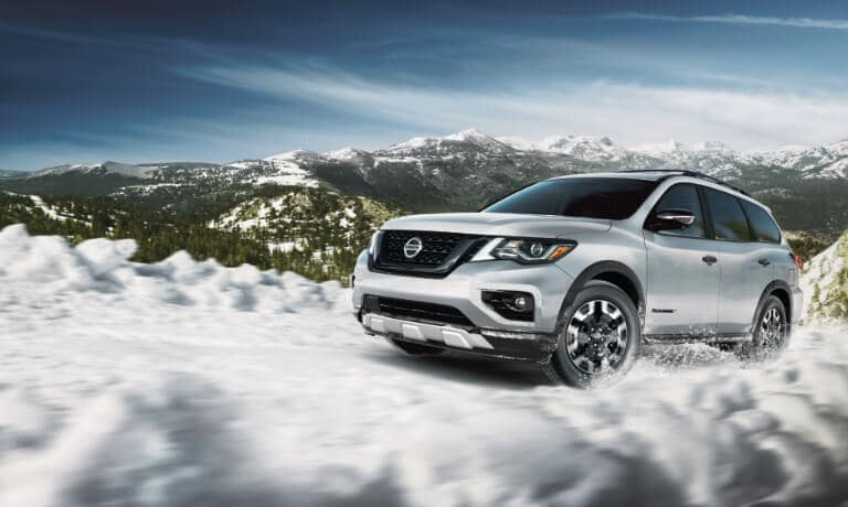 2020 Nissan Pathfinder in white driving off road in the mounitains in the snow