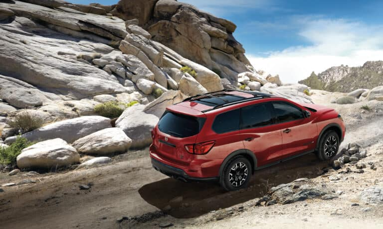 2020 Nissan Pathfinder in red driving off road up a hill in the desert