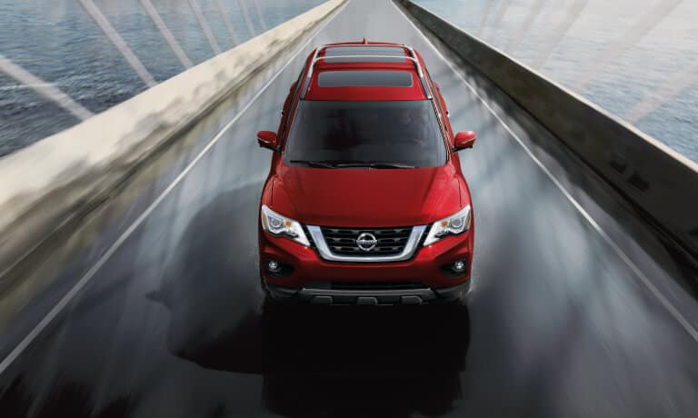 2020 Nissan Pathfinder in red driving on a bridge over the water