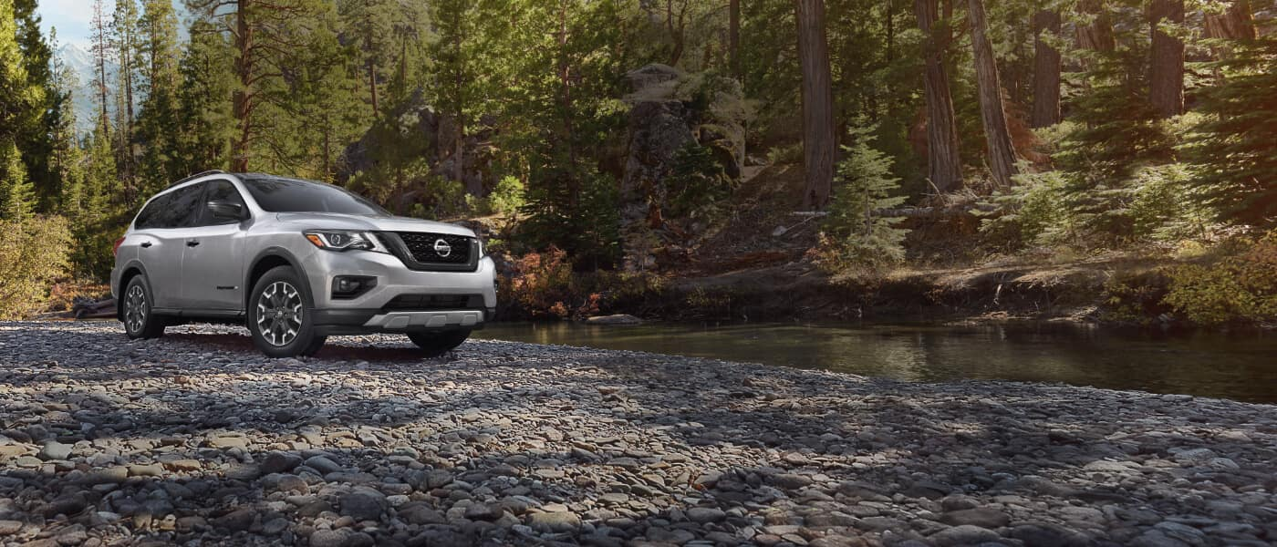 2020 Nissan Pathfinder in silver parked along a river in a forest