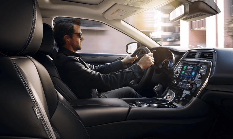 A man driving a Nissan