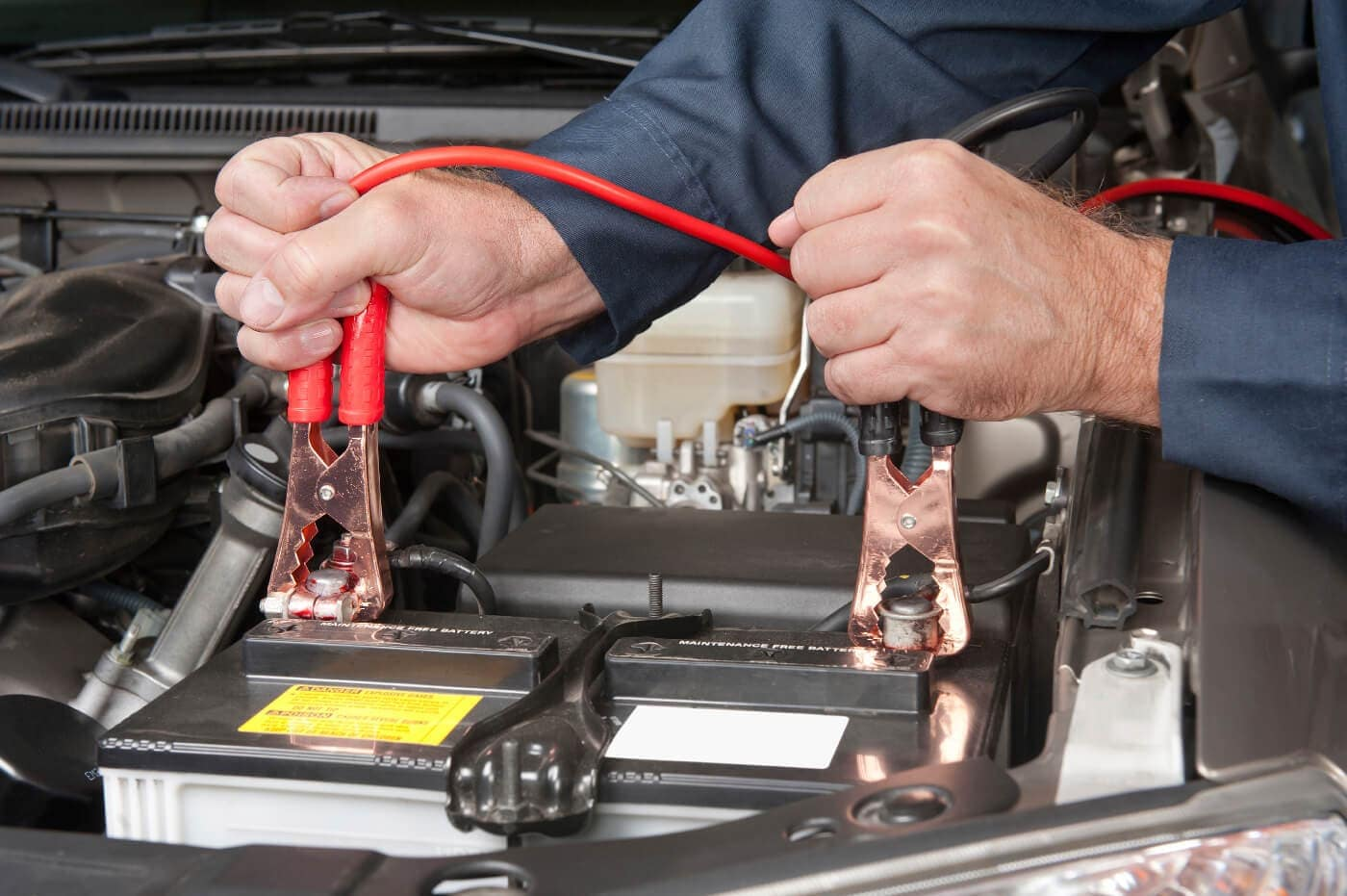 A mechanic charging a car battery