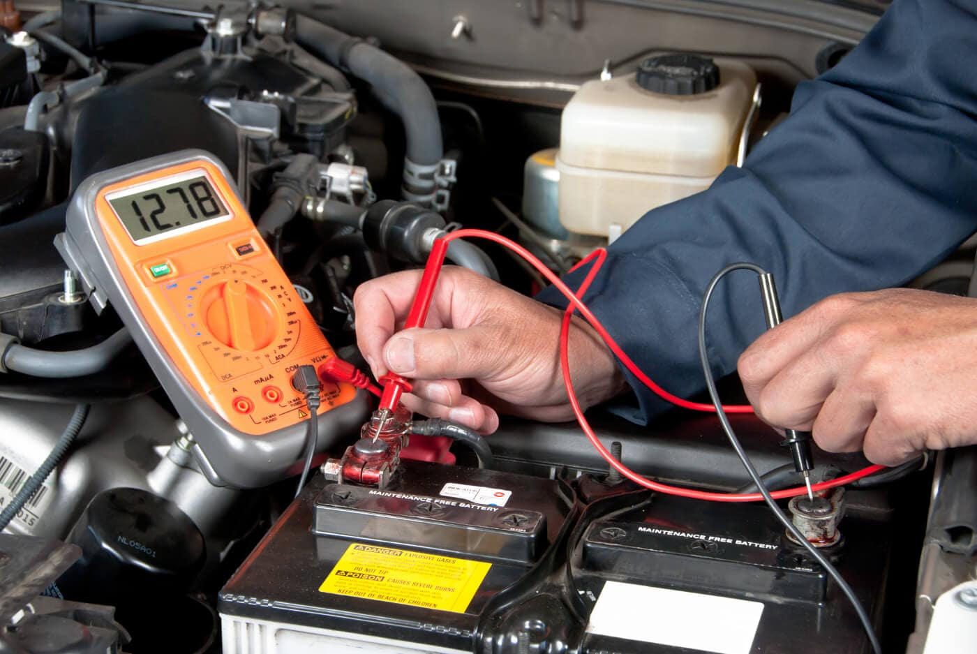 A mechanic testing a car battery