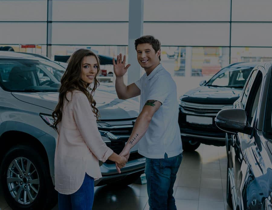man and women holding hands and waving at the camera while standing in the car showroom