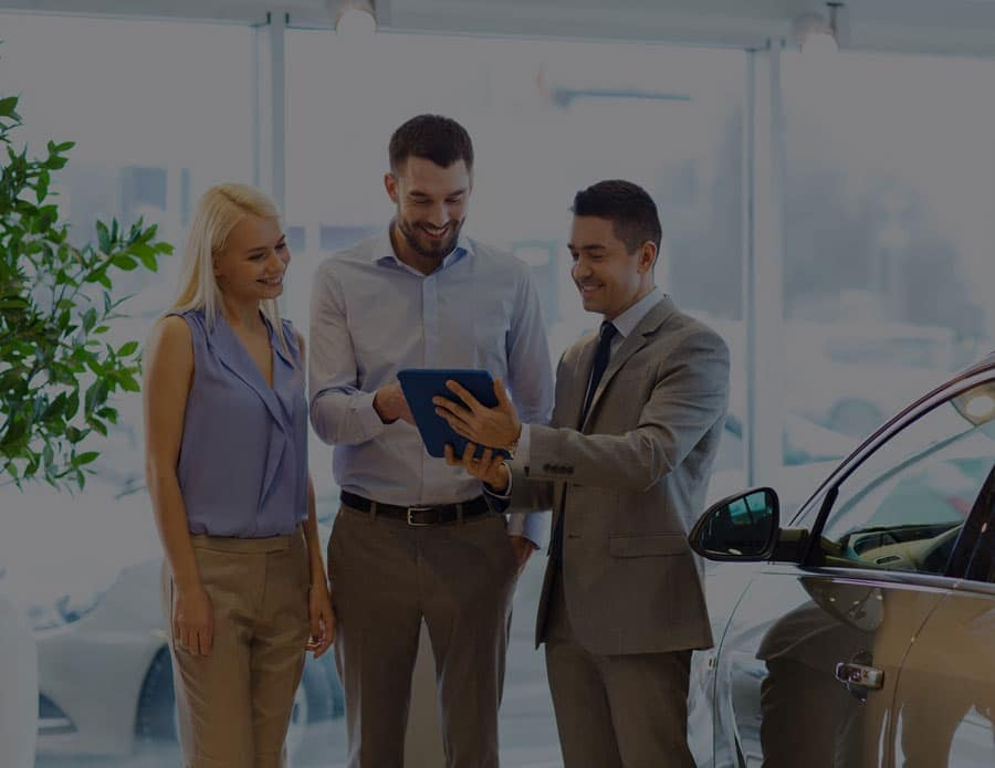 Man and woman standing next to a sales man looking over papers while standing in a car showroom